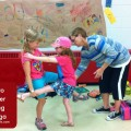 kids do a partner tree pose while a student in the kids yoga teacher training is practice teaching and helping the children figure out how to do the pose