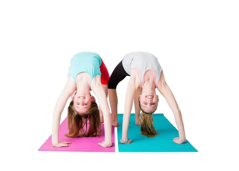 Tweens doing the wheel pose in yoga and learning to master the challenge of difficult poses.